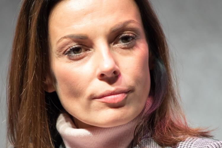 Katarzyna Glinka zasłuchana w kraciastej marynarce