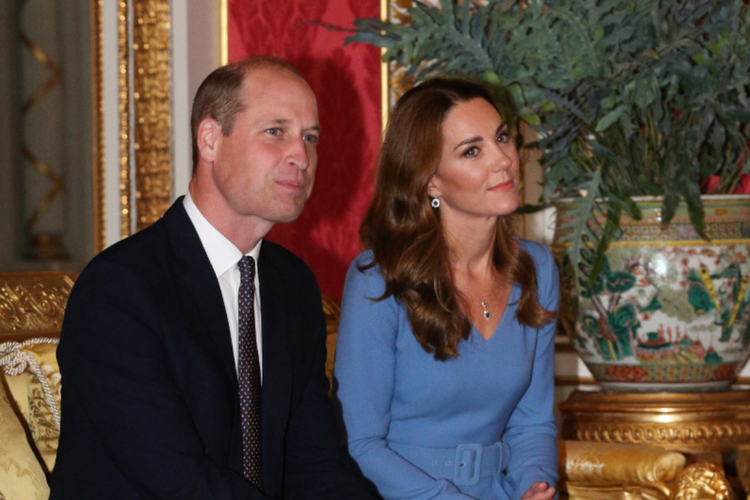 Książę William w garniturze i księżna Kate w niebieskiej sukience siedzą na czerwonej pufie w pałacu