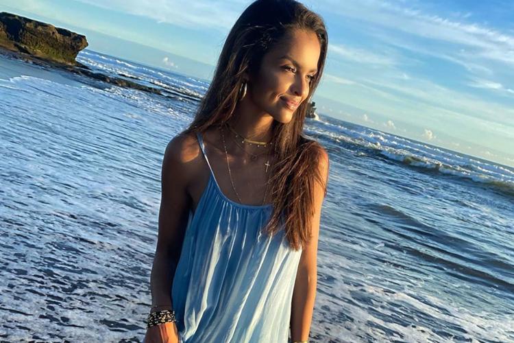 Klaudia El Dursi uśmiechnięta w niebieskiej, letniej sukience nad oceanem o zachodzie słońca