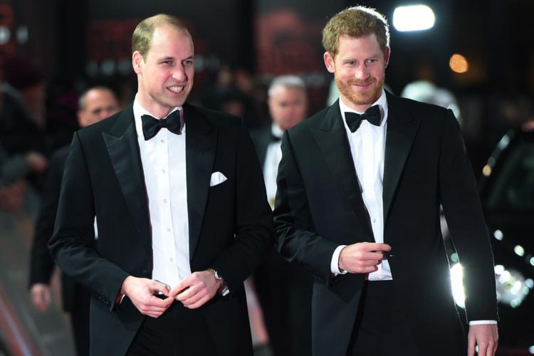 Książę William i książę Harry w czarnych smokingach na czerwonym dywanie