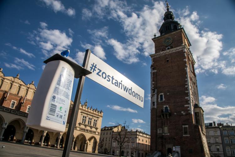 Koronawirus w Polsce: Rynek w Krakowie, a na nim tabliczka z napisem zostań w domu i stojak z mydłem antybakteryjnym