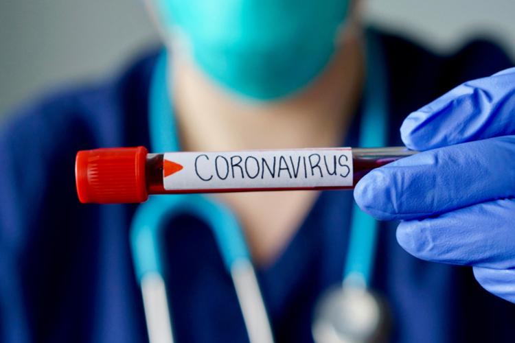 Koronawirus test: fiolka z krwią, którą trzyma w rękach lekarz w maseczce i rękawiczkach