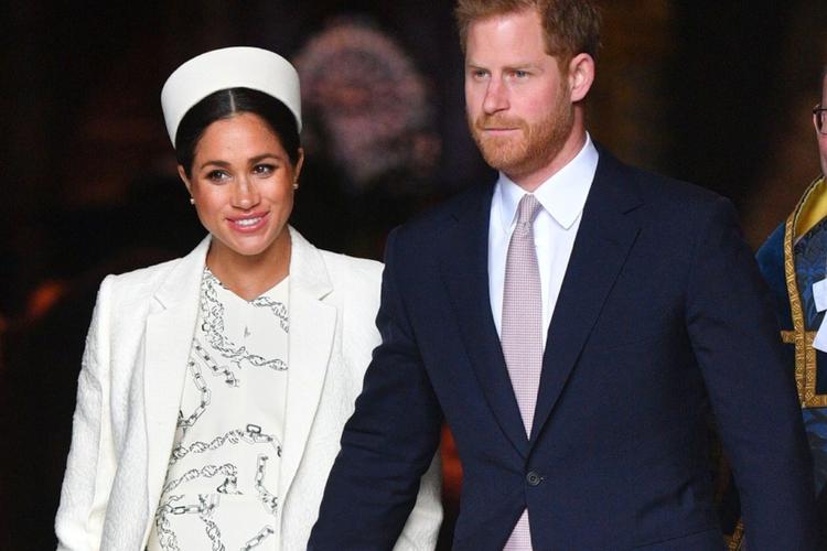 Księżna Meghan w ciąży w białym kostiumie i kapeluszu i książę Harry w garniturze idą za rękę
