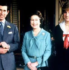 Książę Karol w garniturze, królowa Elżbieta w niebieskiej sukience i księżna Diana w granatowym kostiumie z czerwoną kokardą