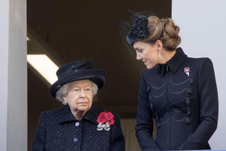 Królowa Elżbieta i księżna Kate ubrane na czarno stoją na balkonie i rozmawiają