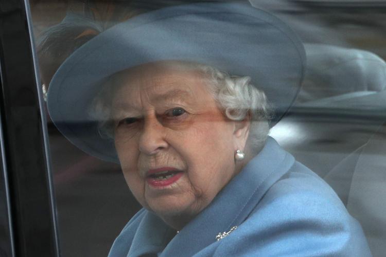 Królowa Elżbieta w samochodzie patrzy przez szybę w stronę fotoreporterów