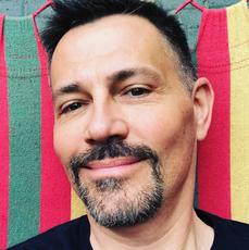 Krzysztof Ibisz w czarnej koszulce leży na kolorowym hamaku