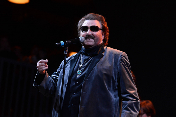 Krzysztof Krawczyk w ciemnych okularach i z krzyżem na szyi na scenie przy mikrofonie podczas koncertu