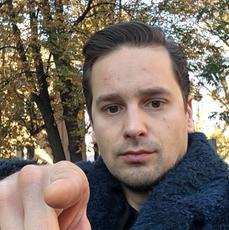 Krzysztof Zalewski wskazuje palcem na obiektyw