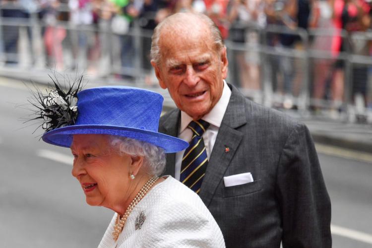 Książę Filip w garniturze uśmiecha się do aparatu stojąc za królową Elżbietą w kapeluszu, która pokazana jest z profilu