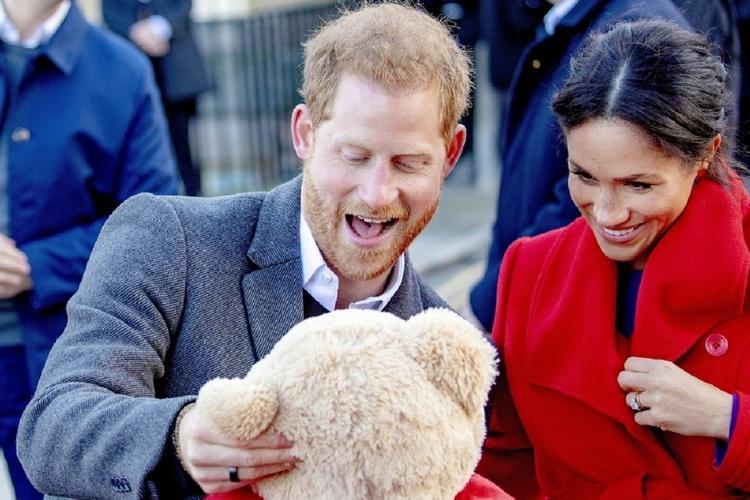 Meghan Markle i książę Harry trzymają pluszowego misia, Są uśmiechnięci.