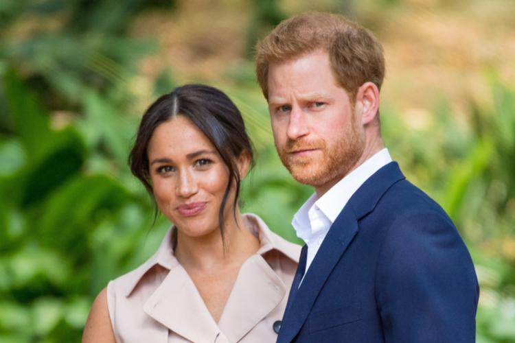 Meghan uśmiechnięta w jasnej sukience i Harry z niepewną miną w granatowym garniturze