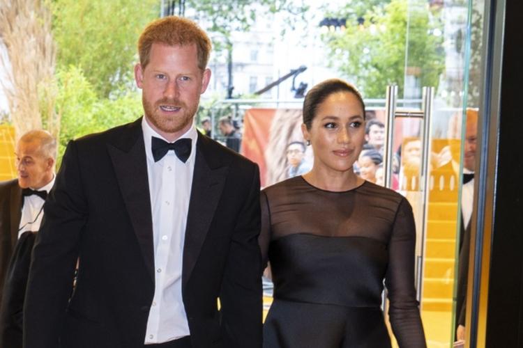 Książę Harry w smokingu i księżna Meghan w czarnej sukience