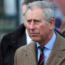 Książę Karol w niebieskiej koszuli i płaszczu