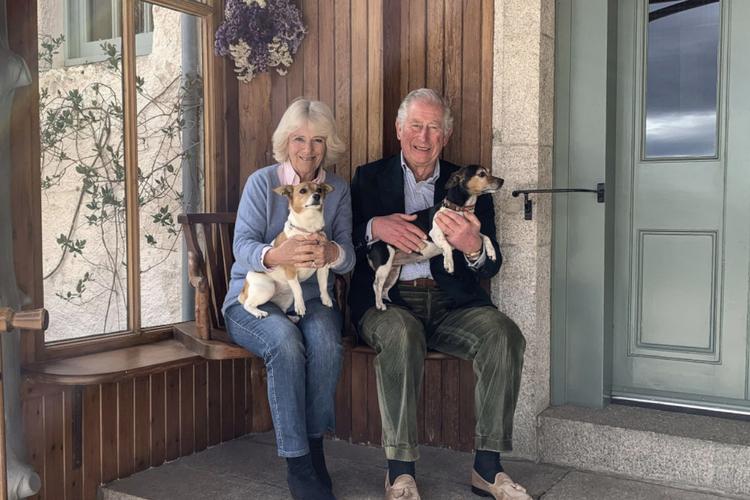 Księżna Camilla i książę Karol z psami przed ich domkiem