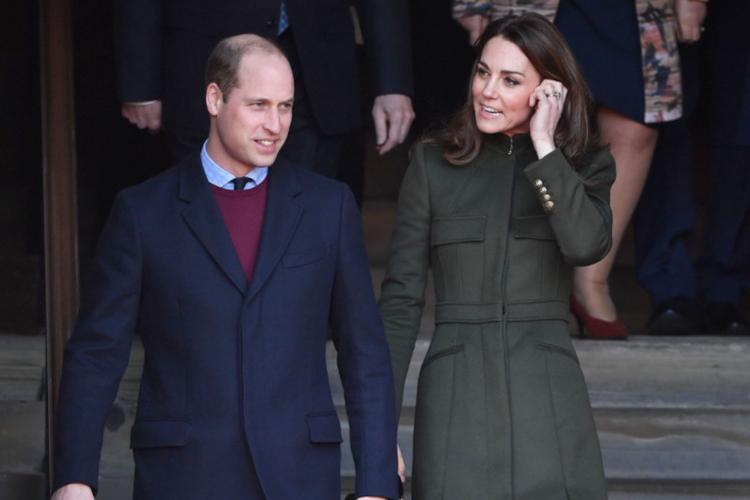 Księżna Kate w płaszczu i książę William w garniturze i płaszczu schodzą po schodach w Bradford