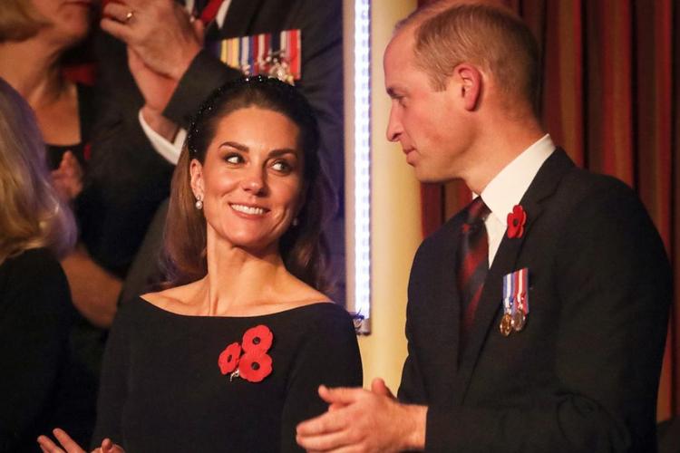 Księżna Kate i książę William w czarnych strojach uśmiechają się do siebie