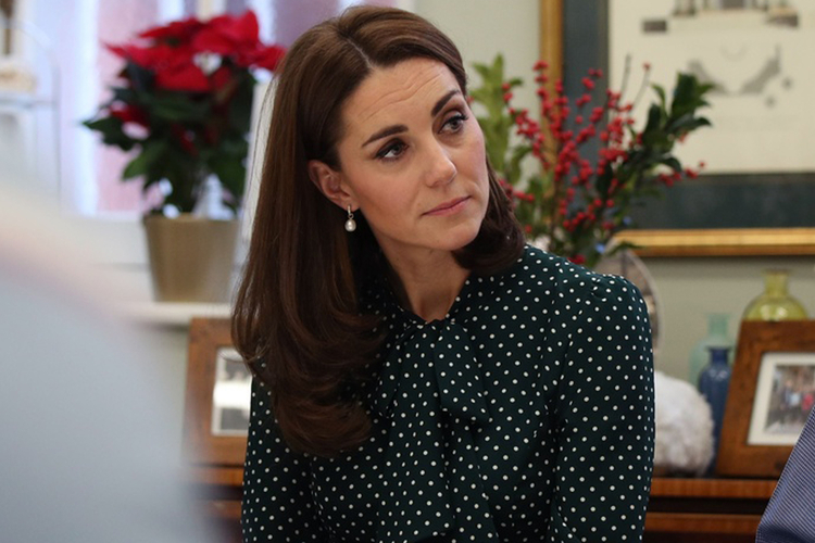 Księżna Kate w zielonej sukience w białe groszki siedzi zasłuchana w rozmowę