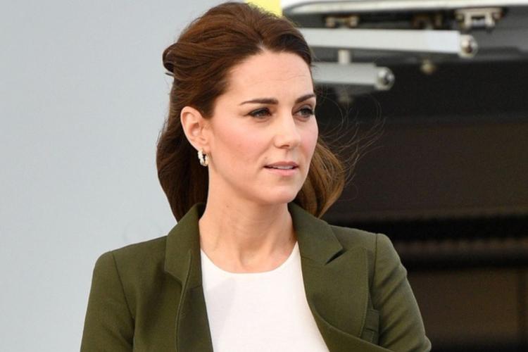 Księżna Kate zapatrzona na lotnisku w marynarce w kolorze khaki, ze spiętymi z tyłu włosami i złotymi kolczykami w uszach
