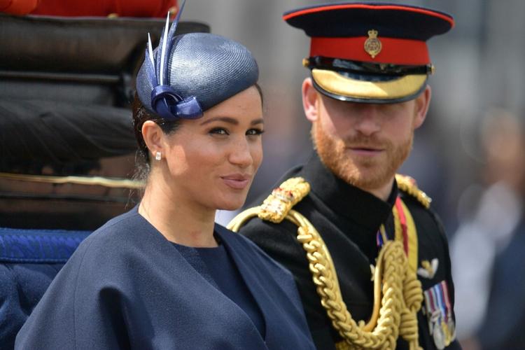 Księżna Meghan w granatowym kapeluszu i książę Harry w mundurze jadą powozem