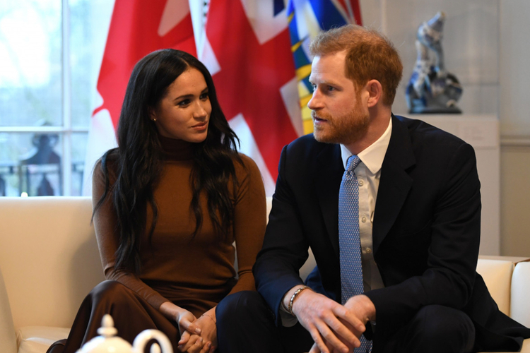 Księżna Meghan w brązowej bluzce i książę Harry w garniturze w kanadyjskiej ambasadzie w Londynie