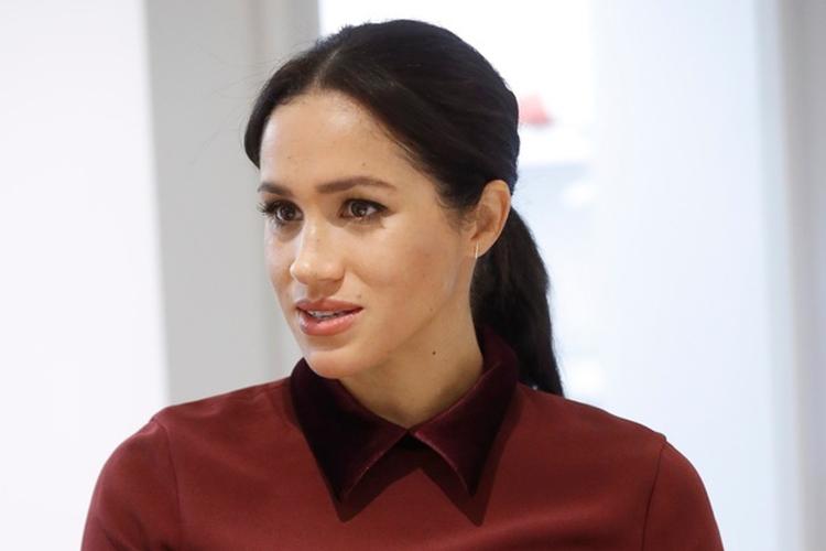 Księżna Meghan w bordowym swetrze i czarnym fartuszku