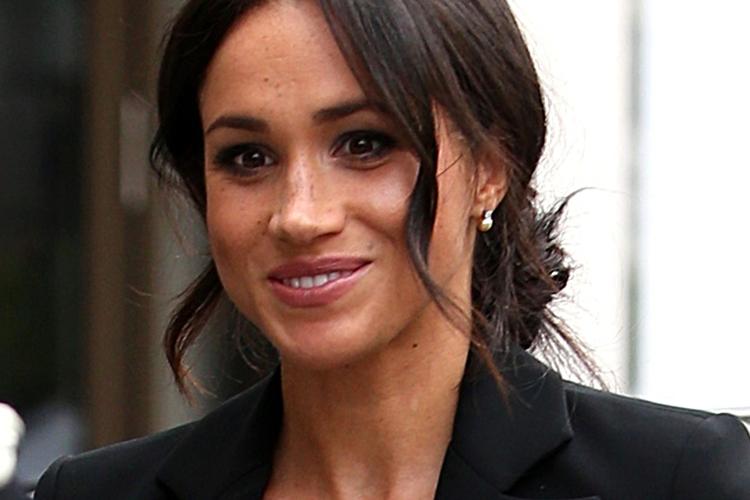 Księżna Meghan w czarnym garniturze uśmiechnięta