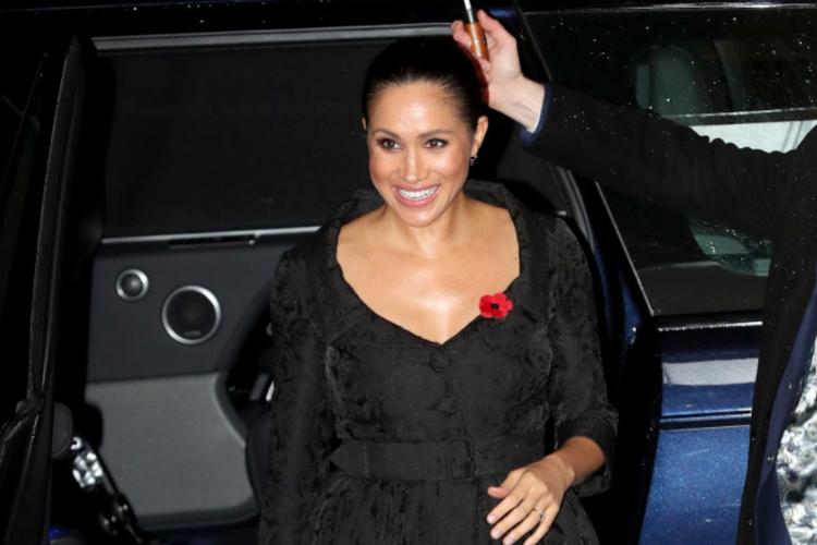 Księżna Meghan w czarnej sukni idzie pod parasolką z limuzyny