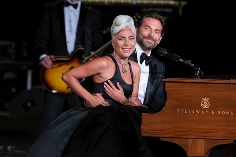 Lady Gaga w czarnej sukni i Bradley Cooper w garniturze obejmujący ją w pasie, siedzą przy fortepianie na gali rozdania Oscarów 2019