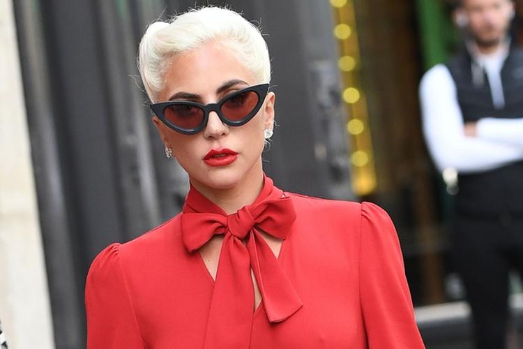 Lady Gaga w czerwonej sukience i okularach idzie po ulicy.