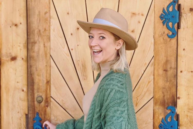 Lara Gessler w kapeluszu na tle drewnianych drzwi w góralskiej chacie