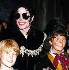 Michael Jackson uśmiechnięty na zdjęciu z dwoma chłopcami