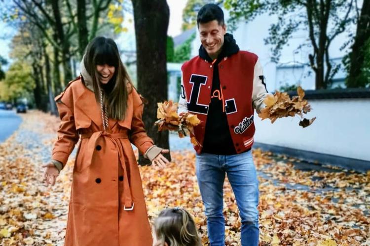 Anna Lewandowska w jesiennym płaszczu, Robert Lewandowski i Klara Lewandowska w parku rzucają liśćmi