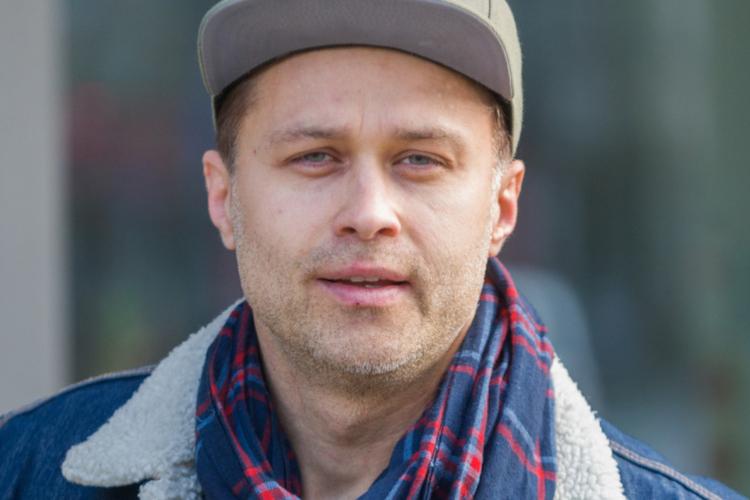 Maciej Zakościelny w jeansowej kurtce, czapce z daszkiem i szaliku