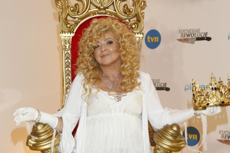 Magda Gessler w białej sukience z koroną na głowie siedzi na czerwonym tronie