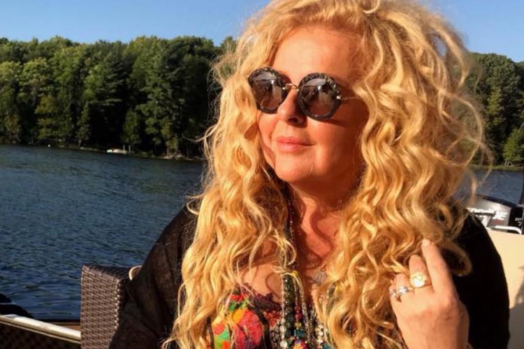 Magda Gessler na łodzi pływa po jeziorze w zachodzącym słońcu