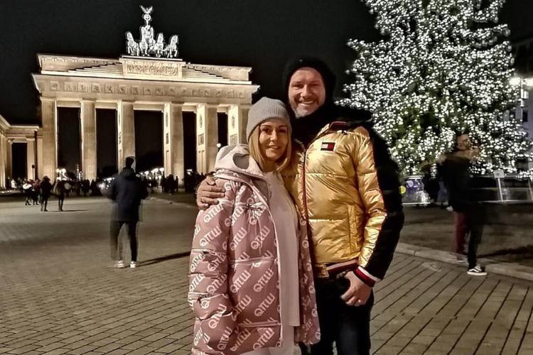 Małgorzata Rozenek-Majdan w puchowej, różowej kurtce i czapce i Radosław Majdan w złoto-czarnej kurtce przy Bramie Brandenburskiej w Berlinie