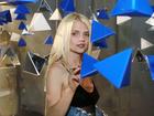 Margaret w czarnej koszulce wśród wiszących trójkątów na evencie Samsunga