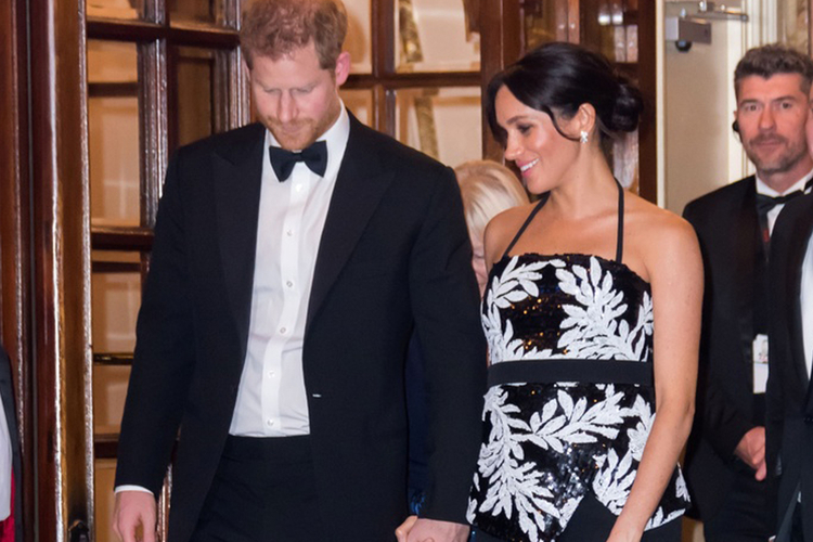Książę Harry w garniturze i księżna Meghan w wieczorowej kreacji z widocznym brzuszkiem ciążowym