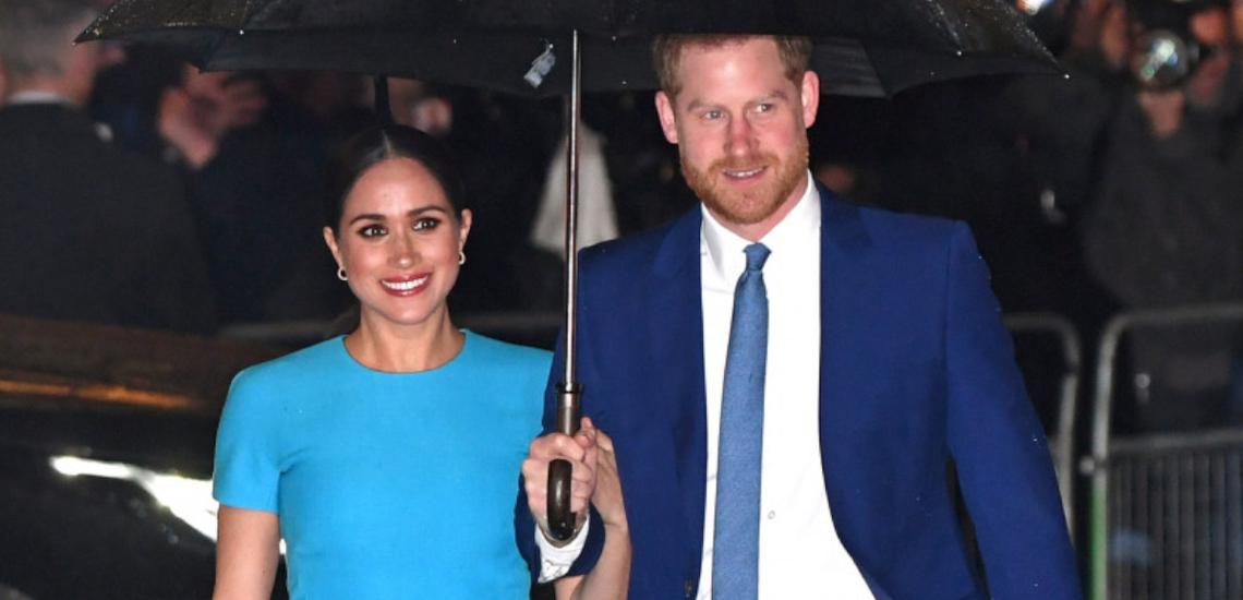 Meghan Markle w niebieskiej sukience i książę Harry w granatowym garniturze idą pod rękę pod czarną parasolką