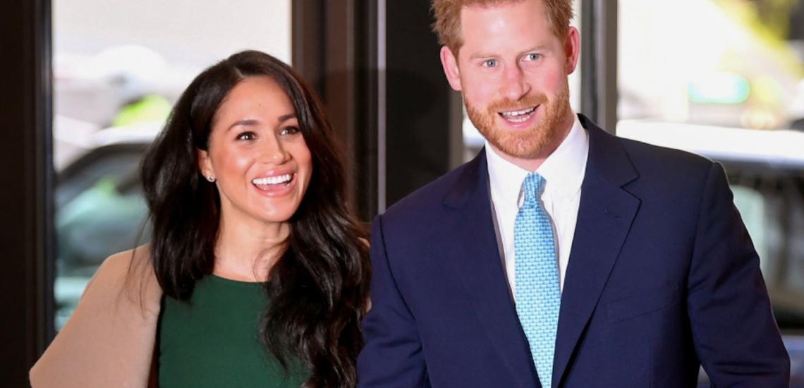 Meghan w zielonej sukience i w płaszczu oraz Harry w garniturze na czerwonym dywanie