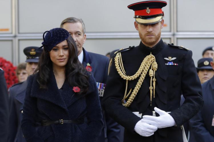 Księżna Meghan w granatowym płaszczu i książę Harry w mundurze podczas pełnienia obowiązków w rodzinie królewskiej