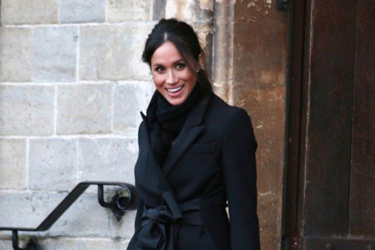 Meghan Markle uśmiechnięta schodzi po schodach w czarnym płaszczu i butach na obcasie