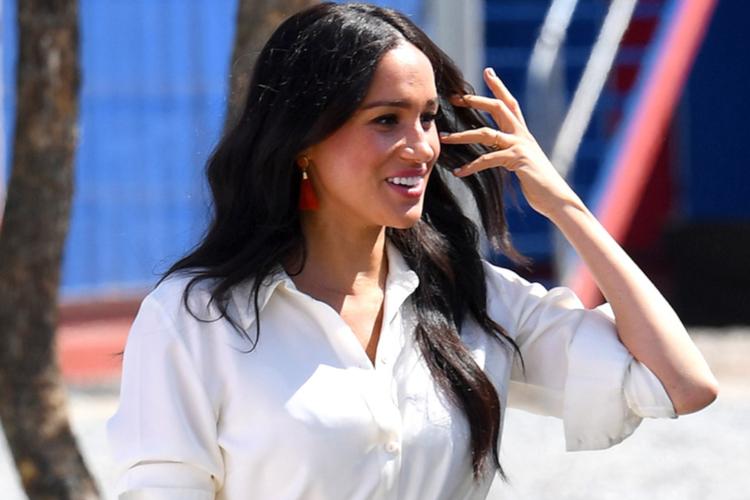Meghan Markle w białej sukience uśmiecha się do zebranych