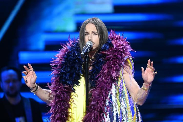 Michał Szpak śpiewa na scenie w szalu boa z fioletowych piór