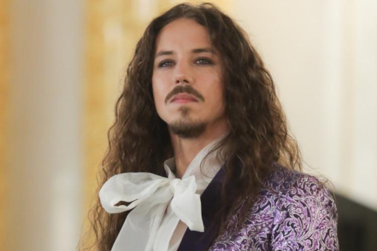 Michał Szpak w fioletowej marynarce i białej koszuli z kokardą