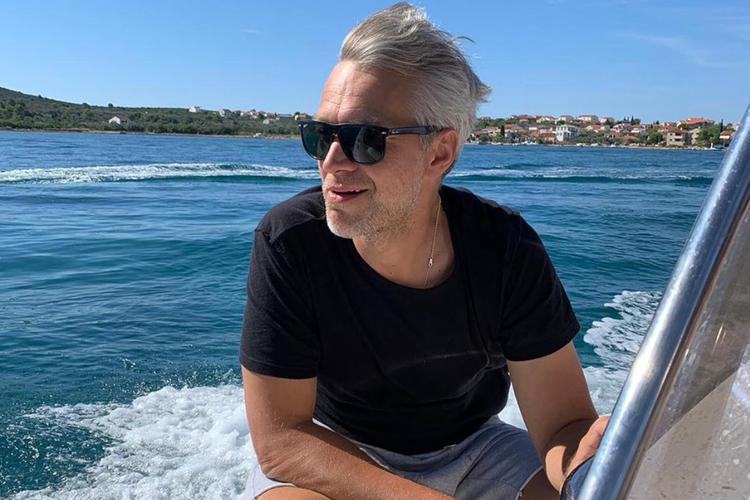 Michał Żebrowski w czarnej koszulce na motorówce z wiatrem we włosach