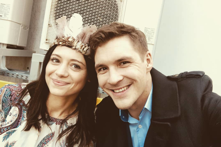 Adriana Kalska w pióropuszu i Mikołaj Roznerski w płaszczu w garderobie