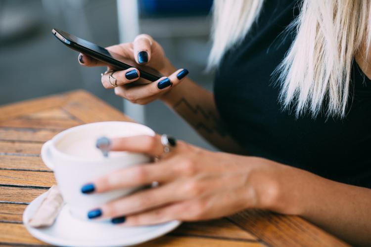 Kobieta wpatrująca się w ekran telefonu