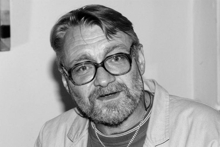 Jacek Czyż z okularami wiszącymi na szyi pozuje do zdjęcia uśmiechnięty
